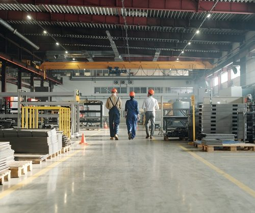 rear-view-three-technicians-engineers-industrial-plant-workwear-leaving-workshop-end-working-day_274679-9594